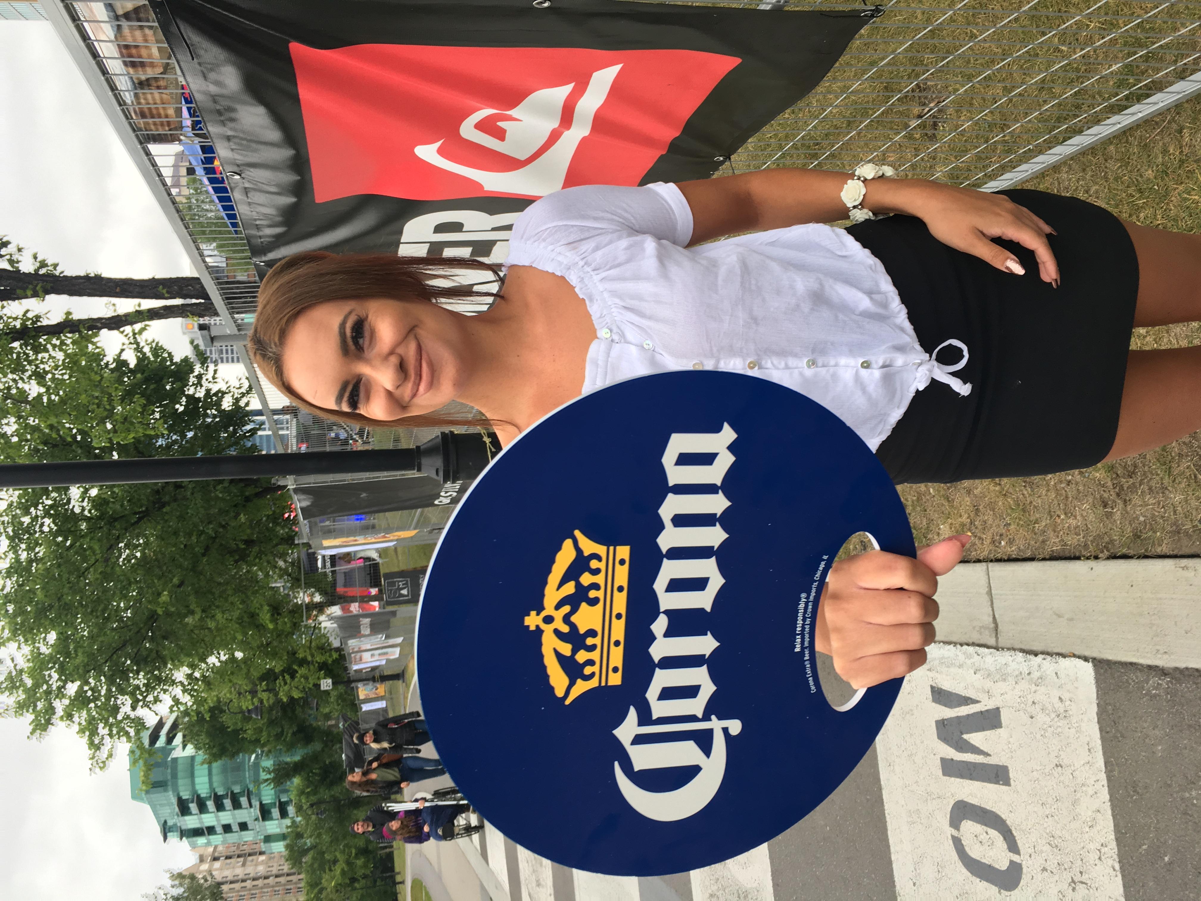 Woman holding Corona signage smiling